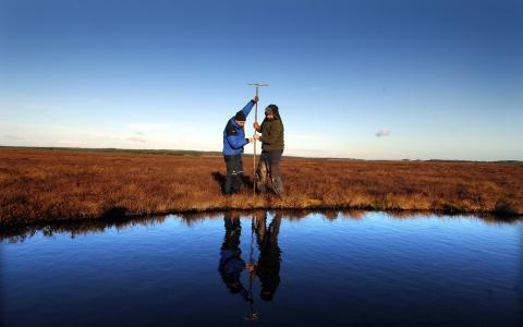 Blawhorn Moss NNR - staff measuring peat depth.© Lorne Gill/NatureScot